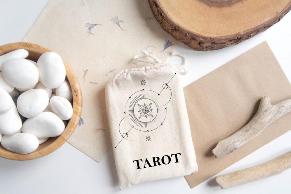 mazo del tarot junta a piedras blancas y madera
